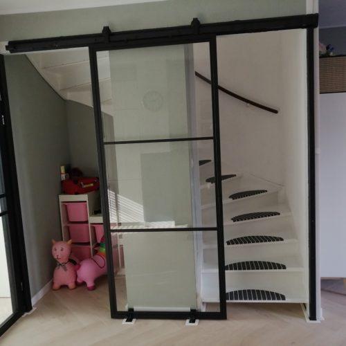 Stalen schuifdeur open voor de trap